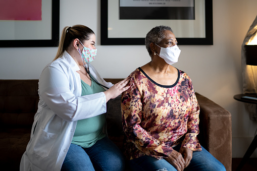 Doctor using stethoscope listening to senior patient breathing at her house - using face mask