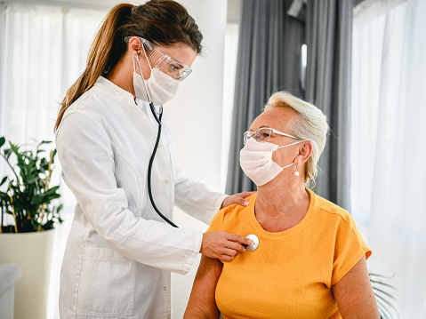 Doctor using stethoscope listening to senior patients breathing