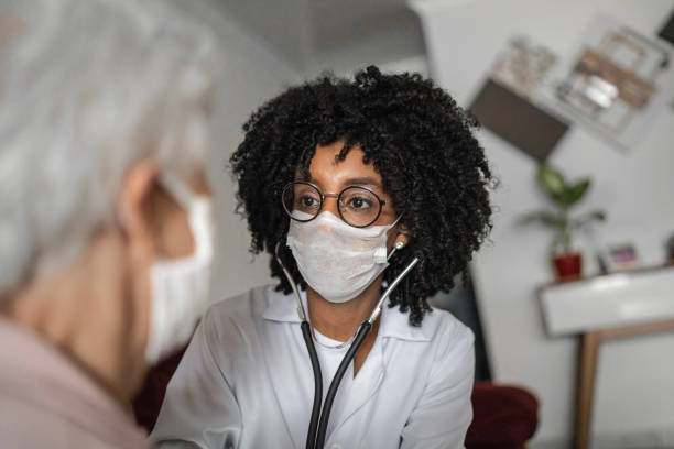 doctor using stethoscope on a senior patient at home - afro latino mask imagens e fotografias de stock