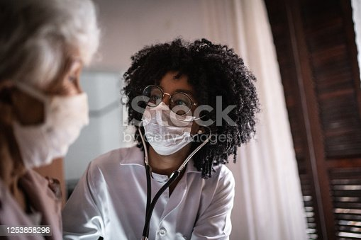 Doctor using stethoscope on a senior patient at home