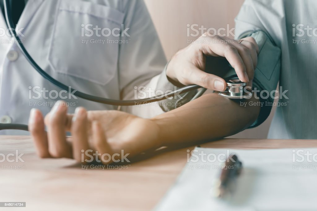 Doctor using stethoscope take a tap on the patient's arm. stock photo