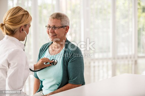 Female doctor listening senior woman's heartbeat during routine medical examination.