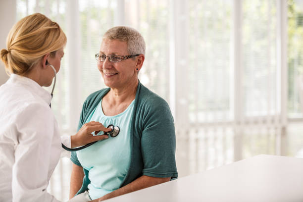 Doctor using stethoscope while examining patient stock photo