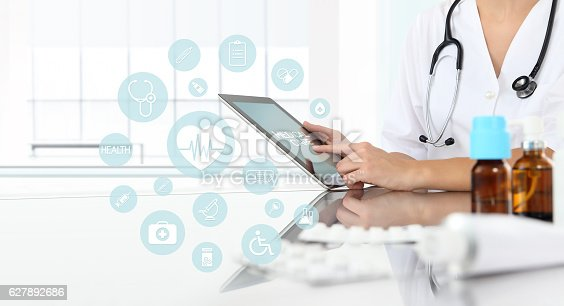 istock doctor using tablet in medical office with icons 627892686