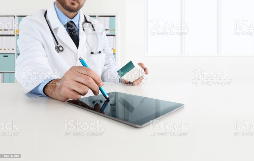 doctor using tablet on desk prescribes the medicine stock photo