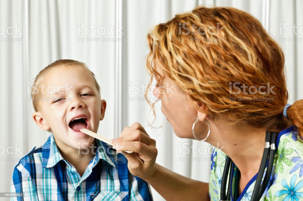 Doctor Using Tongue Depressor to Check Young Boys Throat royalty-free stock photo