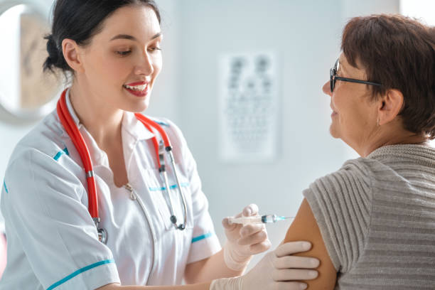 Doctor vaccinating a woman stock photo
