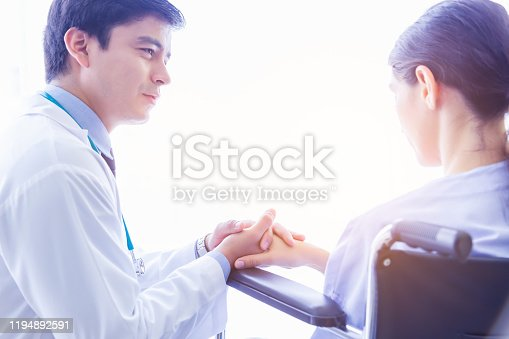 1041630080istockphoto Doctor visit patient telling patient that she gets cancer. Doctor comforting, consoling, encourage by holding patients hand and ensuring would be safe. Patient get depressed, stress, sad on wheelchair 1194892591