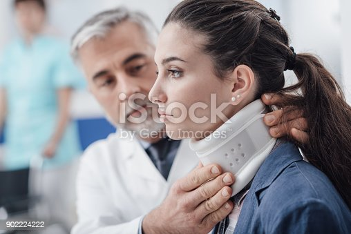Professional doctor visiting a young injured patient at the hospital, he is adjusting her cervical collar