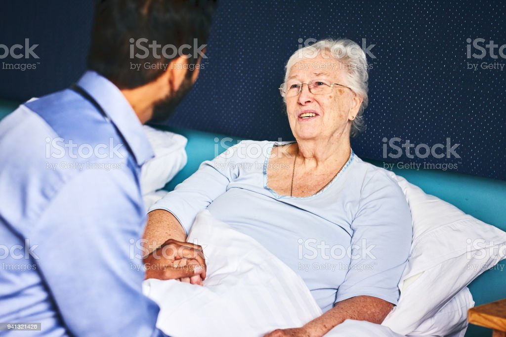 Senior woman lying on bed with male doctor holding her hand...