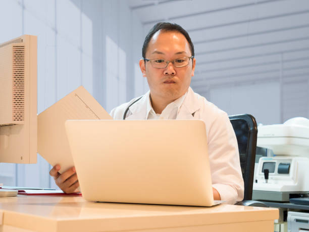 Doctor watching PC and patient data. stock photo