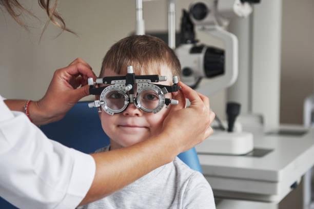 Arzt trägt eine Brille zu einem Kind. Kleiner Junge mit Phoropter, der seine Augen in der Arztpraxis getestet hat – Foto