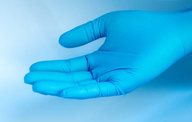 doctor wearing blue rubber glove stock photo