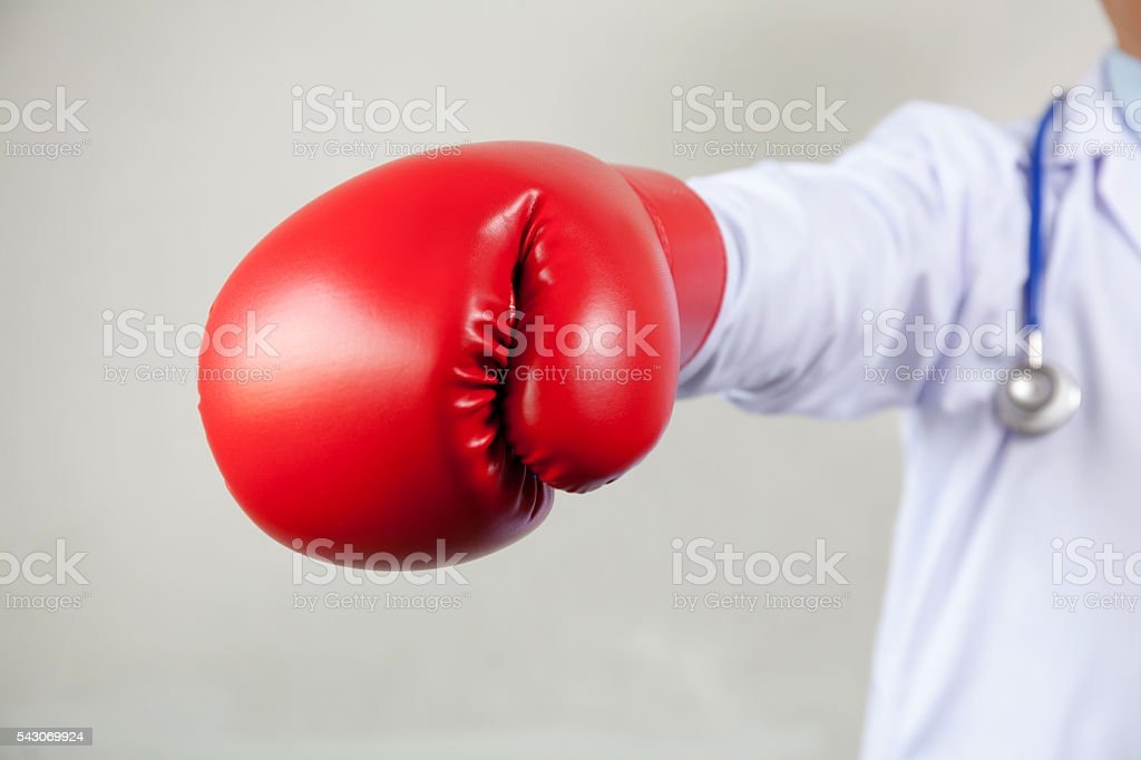 Doctor wearing boxing gloves in white background stock photo