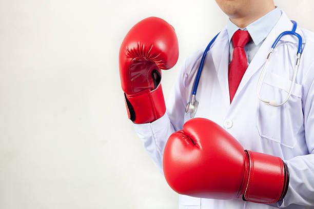 doctor wearing boxing gloves in white background - immunsystem stärken stock-fotos und bilder