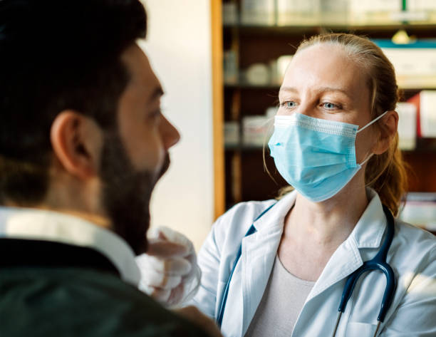 Doctor wearing face mask examining male patient stock photo