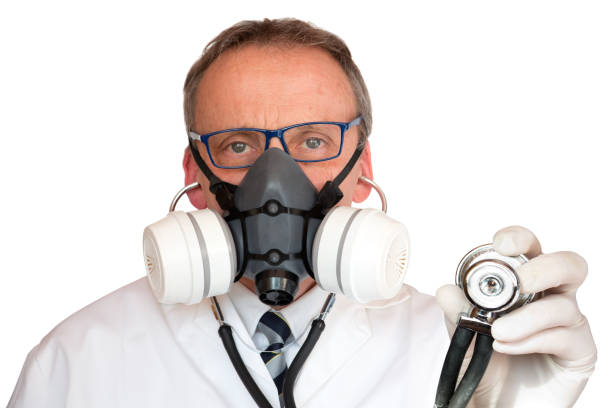 Doctor Wearing Face Mask holding stethoscope looking at camera stock photo
