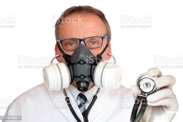 Doctor Wearing Face Mask Holding Stethoscope Looking At Camera Stock Photo - Download Image Now