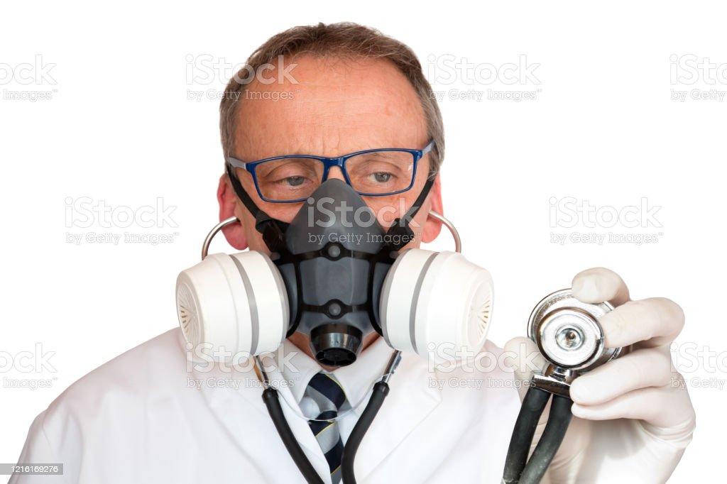 Doctor Wearing Face Mask holding stethoscope looking at stethoscope Doctor wearing face mask in lab-coat with stethoscope, holding stethoscope looking at stethoscope, isolated on white. Adult Stock Photo