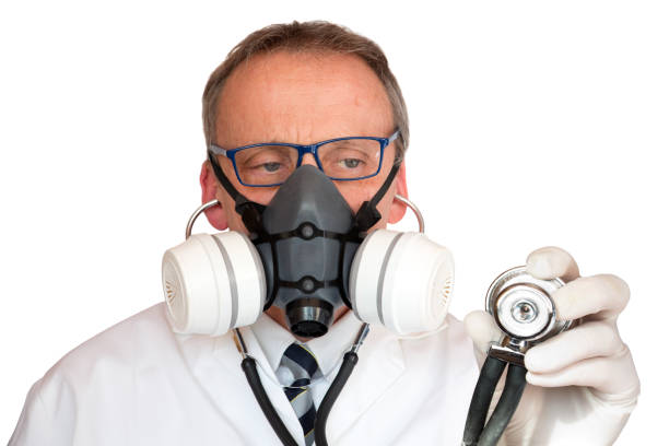Doctor Wearing Face Mask holding stethoscope looking at stethoscope stock photo