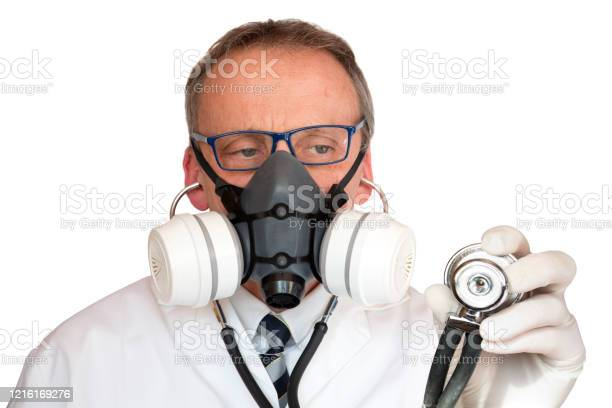 Doctor Wearing Face Mask Holding Stethoscope Looking At Stethoscope Stock Photo - Download Image Now