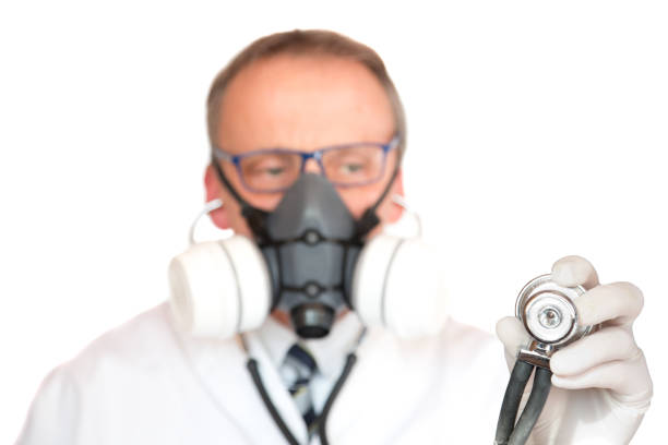 Doctor Wearing Face Mask with focus on stethoscope stock photo