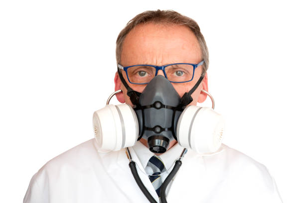 Doctor Wearing Face Mask with stethoscope in ears stock photo