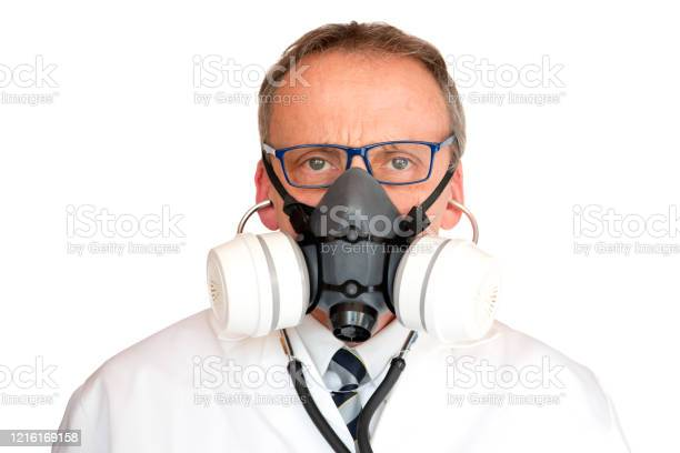 Doctor Wearing Face Mask With Stethoscope In Ears Stock Photo - Download Image Now