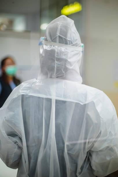 Médico usando roupas protetoras contra o novo, expandindo rapidamente Coronavirus. - foto de acervo