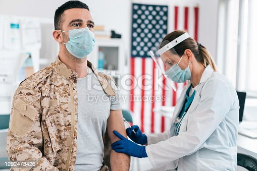 Nurse vaccinates a soldier with COVID-19 vaccine. Prevention and immunization from coronavirus infection