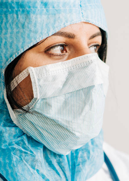 Doctor wearing protective workwear looking away stock photo