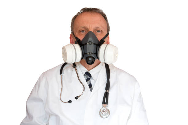 Doctor Wearing Rubber Face Mask in lab-coat stock photo