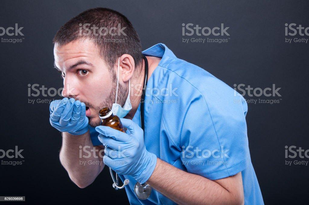 Doctor wearing scrubs taking pills from bottle like hiding stock photo