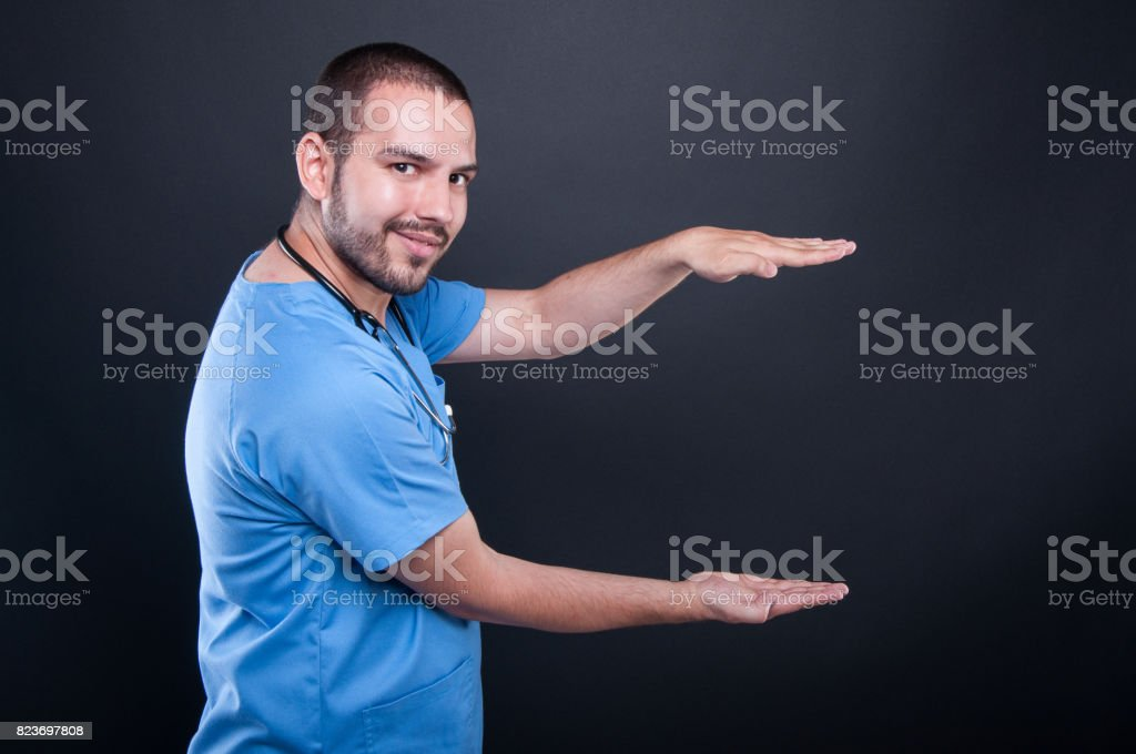 Doctor wearing scrubs with stethoscope holding copypsace both hands stock photo
