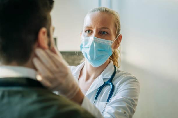 남자를 검사하는 외과 마스크를 착용하는 의사 - 의사 뉴스 사진 이미지