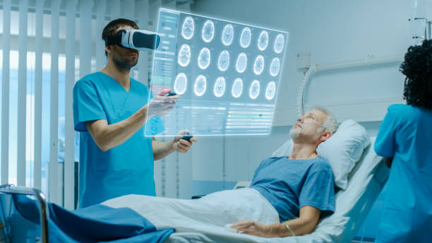 Doctor Wearing Virtual Reality Headset and Holding Joysticks Cures Senior Patient who is Lying in Bed. He Uses Augmented Reality Interface, Looks at Brain Scans and Medical History. Nurse Does Checkup Doctor Wearing Virtual Reality Headset and Holding Joysticks Cures Senior Patient who is Lying in Bed. He Uses Augmented Reality Interface, Looks at Brain Scans and Medical History. Nurse Does Checkup training equipment stock pictures, royalty-free photos & images