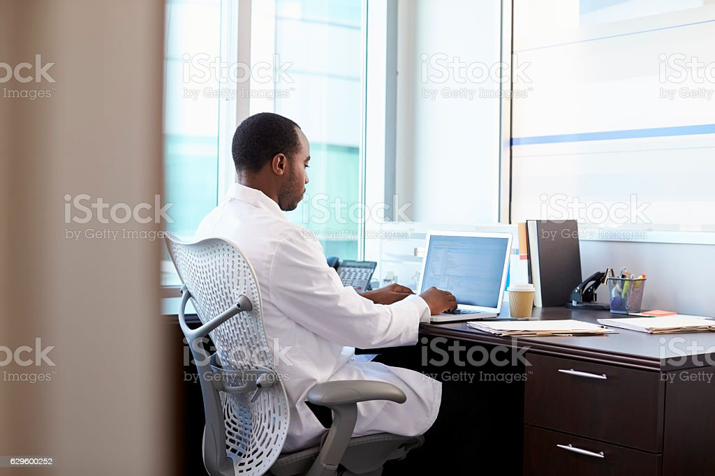 Doctor Wearing White Coat Working On Laptop In Office stock photo