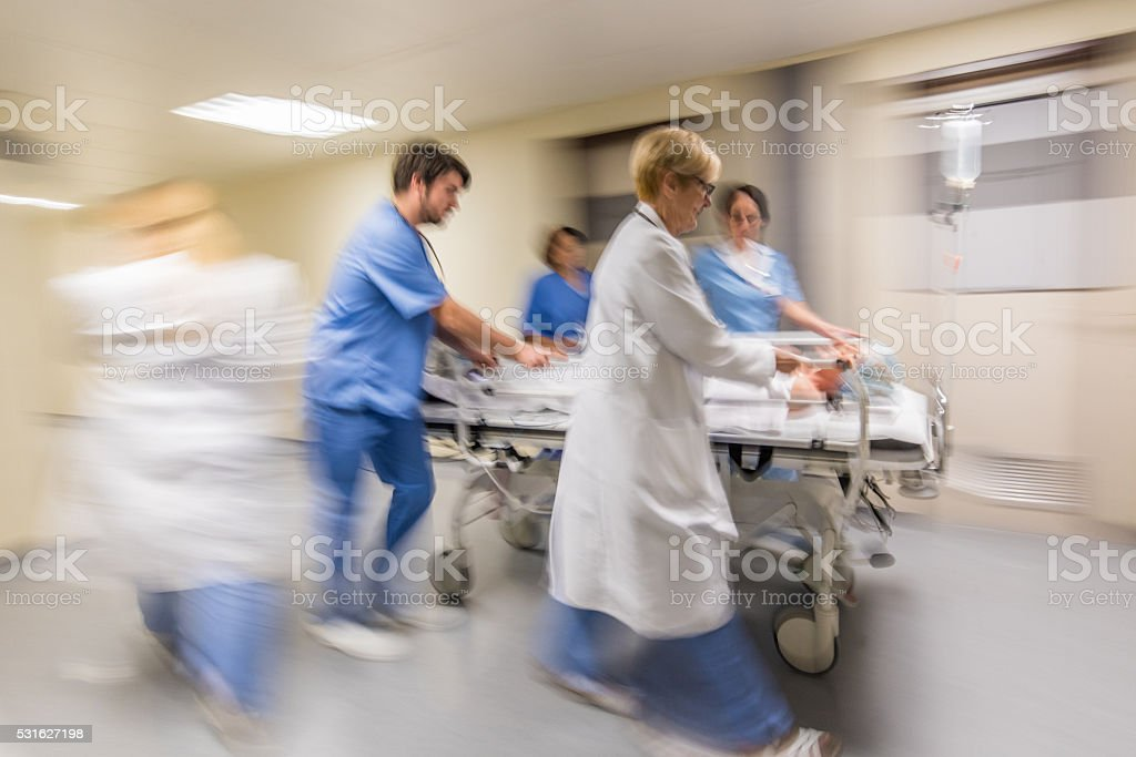 Doctor wheeling patient stock photo