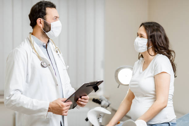 Doctor with a pregnant woman in medical masks during an examinations stock photo