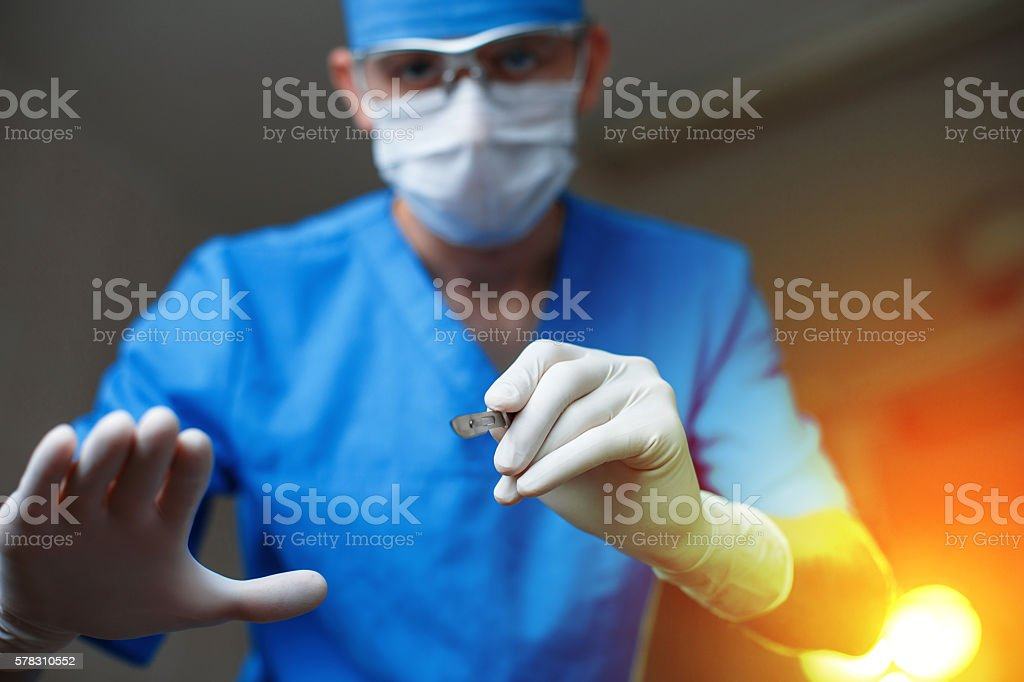 Doctor with a scalpel against a bright light. Modern surgeon - foto de stock