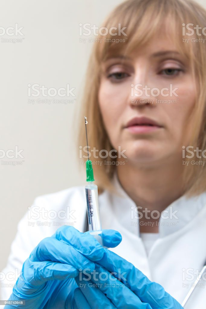 A doctor with a stethoscope around her neck and a syringe in her hand is standing and holding a syringe with blue gloves and prepares an injection. stock photo