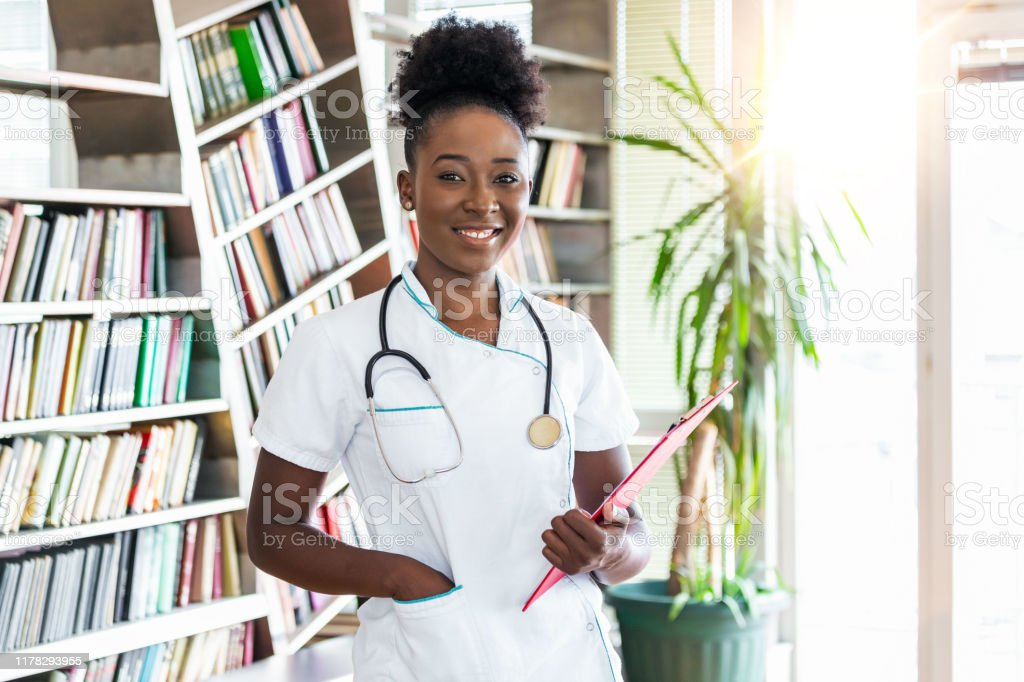 Doctor with a stethoscope, holding a notebook in her hands. African...