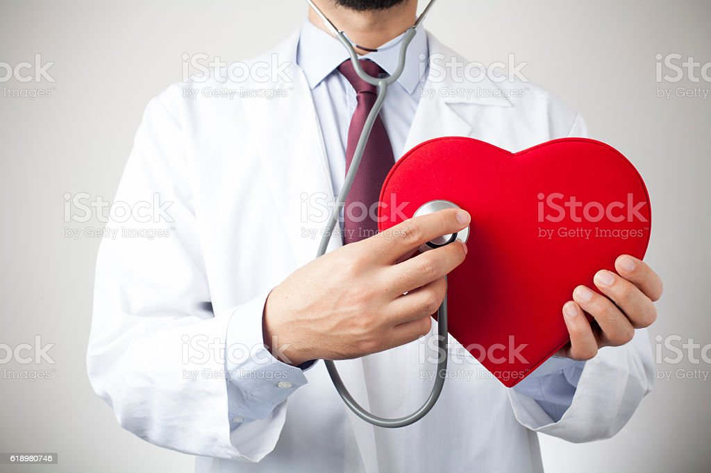 doctor with a stethoscope holding heart stock photo