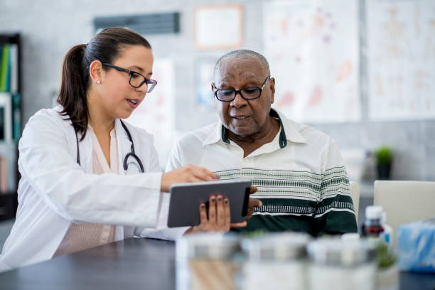 doctor with a tablet computer - geriatrics stock pictures, royalty-free photos & images
