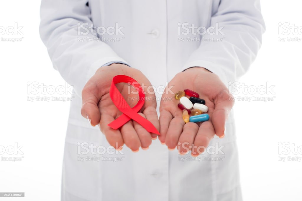 doctor with aids ribbon and pills stock photo