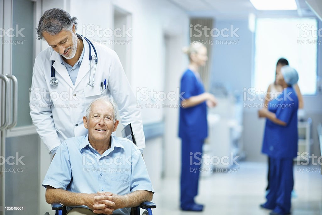 Doctor with an old man sitting in wheelchair royalty-free stock photo