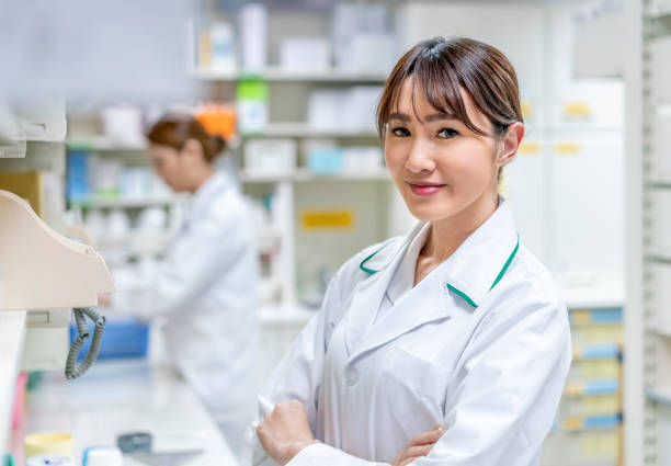 Doctor with arms crossed standing in pharmacy stock photo