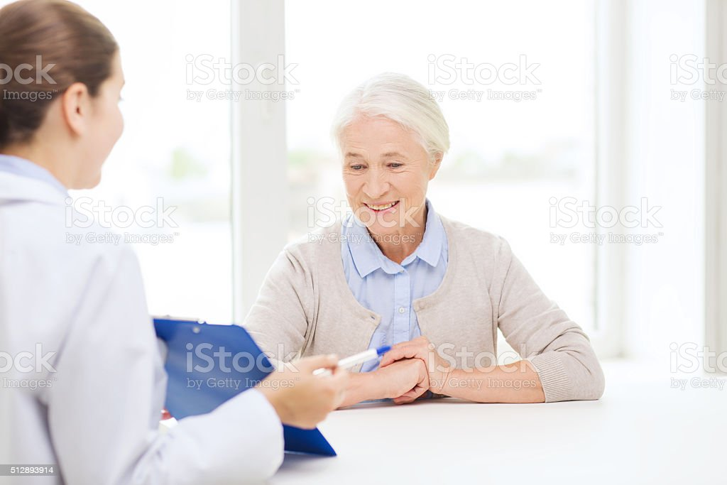 doctor with clipboard and senior woman at hospital stock photo