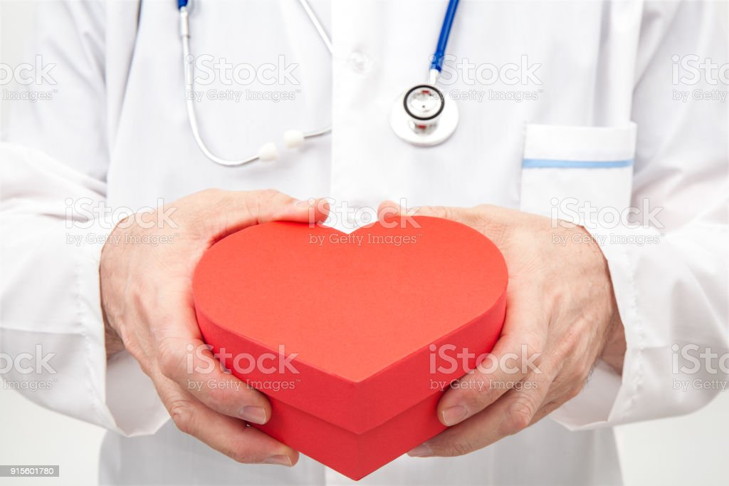 Doctor with Closed Red Gift Box in Hands stock photo