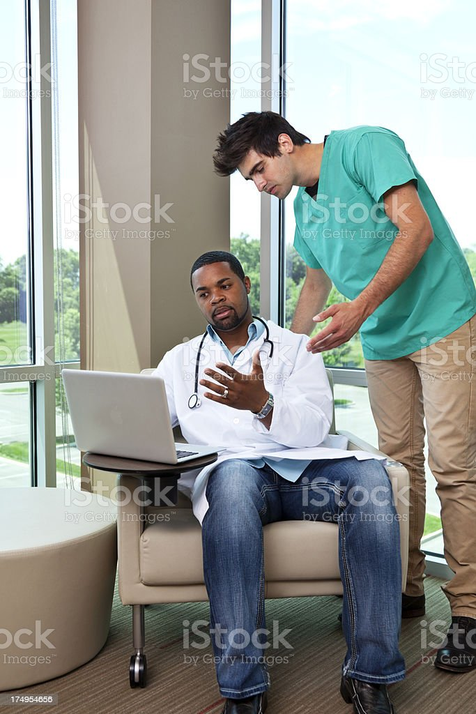 Doctor with computer demonstrating to paramedic. royalty-free stock photo